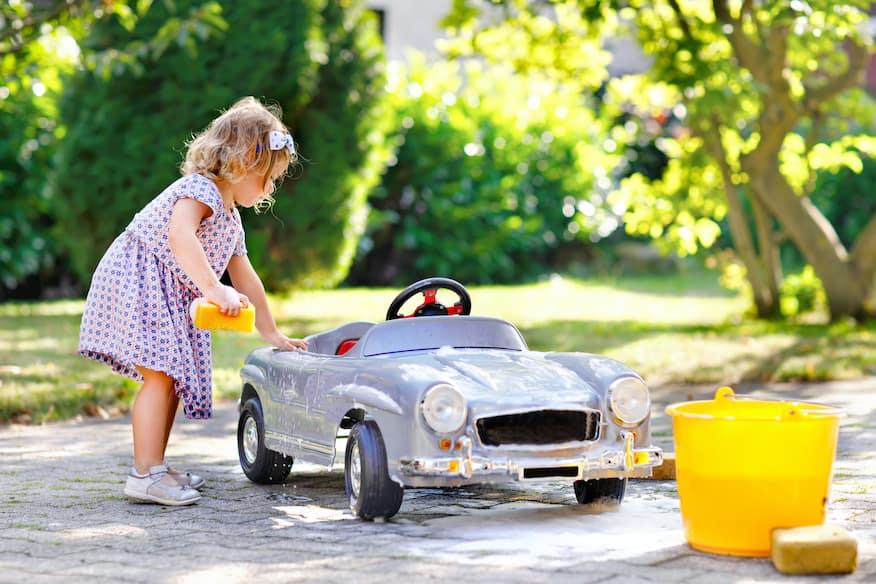 Little girl washing a toy car